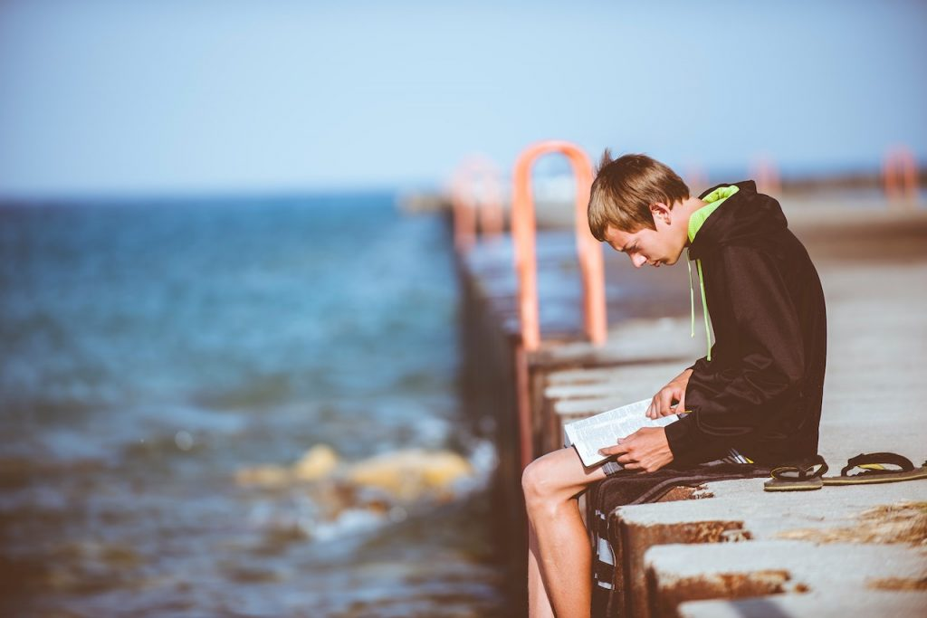 Boy reading sitting on a pier